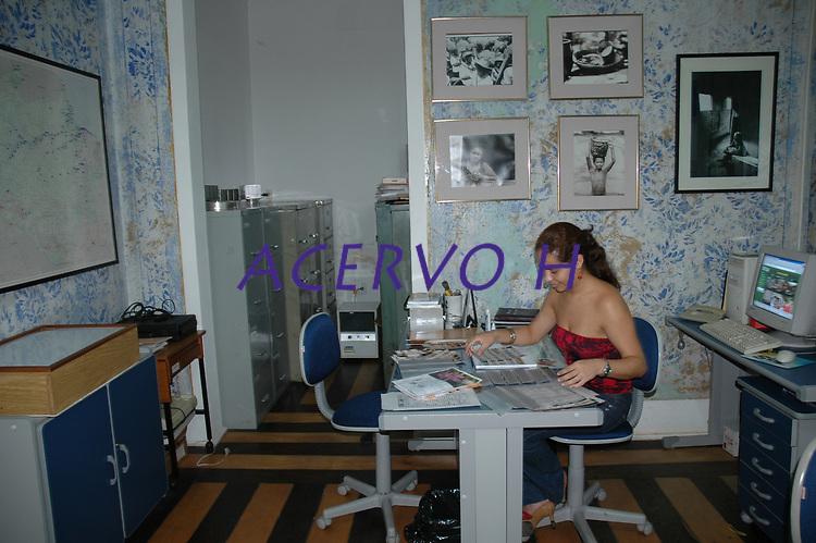 Angélica Fidéllis nossa pesquisadora iconográfica executando tarefas diárias.<br /> <br /> Ao fazer pequena reforma na sala de nosso acervo descobrimos a pintura original do imóvel. Cconstruído entre as décadas de 1920 e 1930 , a sala era pintada com flores azuis e vermelhas, mas a segunda tinta totalmente esmaecida.<br /> Foto Paulo Santos<br /> 09/2004