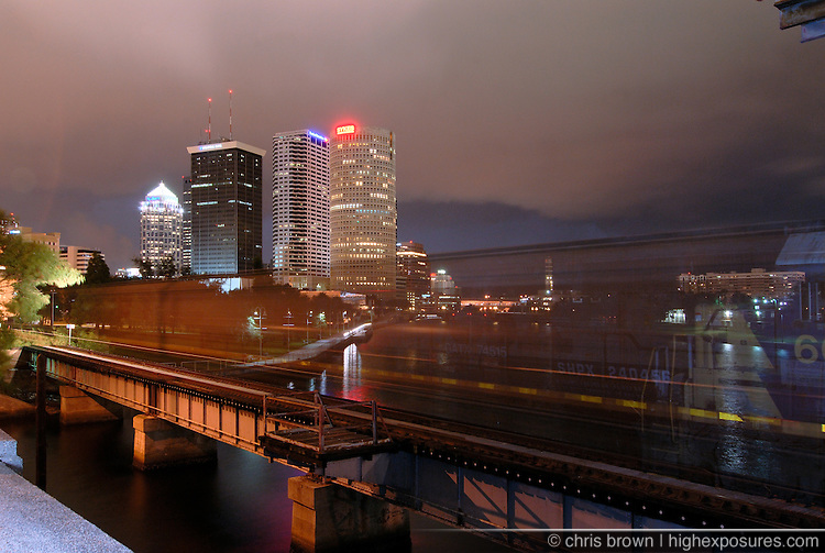 A freight train rolls across the Hillsborough River in Tampa at night.