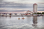 Scenery of people kayaking at Nanaimo city waterfront in the eveninng with the harbour and the city skyline in the background. Vancouver Island, British Columbia, Canada 2017