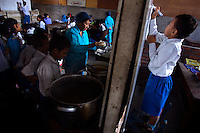 "Students of Kartini Emergency School line up for their meal assisted by the 'Twin Teachers'. As part of the ""life skills"" training, teams of students are formed, to give all students the oportunity to cook food for the school. Since the early 1990s, twin sisters Sri Rosyati (known as Rossy) and Sri Irianingsih (known as Rian) have used their family inheritance to set up and run 64 schools in different parts of Indonesia, providing primary education combined with practical skills to some of the country's most deprived children."