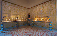 Cabinets of goblets and of monstrances, with blue and gold glass beads made with Murano glassmaker Salviati, in the Bell tower room themed 'Le Merveilleux' or The Supernatural, first floor, in Le Tresor de la Cathedral d'Angouleme, in Angouleme Cathedral, or the Cathedrale Saint-Pierre d'Angouleme, Angouleme, Charente, France. The 12th century Romanesque cathedral was largely reworked by Paul Abadie in 1852-75. In 2008, Jean-Michel Othoniel was commissioned by DRAC Aquitaine - Limousin - Poitou-Charentes to display the Treasure of the Cathedral in some of its rooms, which opened to the public on 30th September 2016. The cement floor tiles made by MiraColour and the hand printed wallpaper by Atelier d'Offard, both use interlacing patterns reminiscent of the Neo-Romanesque period of the 19th century. Picture by Manuel Cohen. L'autorisation de reproduire cette oeuvre doit etre demandee aupres de l'ADAGP/Permission to reproduce this work of art must be obtained from DACS.