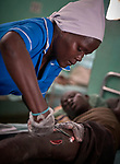Nurse Nacima Keni cleans a patient's wound in the Mother of Mercy Hospital in Gidel, a village in the Nuba Mountains of Sudan. The area is controlled by the Sudan People's Liberation Movement-North, and frequently attacked by the military of Sudan. The Catholic hospital is the only referral hospital in the war-torn area.<br /> <br /> Keni is a 2015 graduate of the Catholic Health Training Institute, a school in Wau, South Sudan, sponsored by Solidarity with South Sudan.
