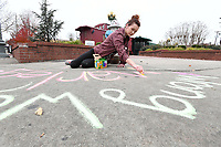NWA Democrat-Gazette/J.T. WAMPLER Ashlee Armstrong of Fayetteville does some guerrilla marketing Monday Nov. 13, 2017 by chalking an advertisement on the sidewalk. Armstrong was at the corner of Dickson St. and West Ave. and was advertising for Marley's Pizzeria on Dickson St. where she works as a server.