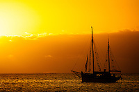 A sailing boat at sunset at the surf break of St Leu on Reunion  Island in the southern Indian Ocean.  Photo Joli