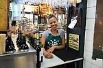 Smiling barmaid inside famous historic Los Gatos Cervecerias bar, Madrid city centre, Spain