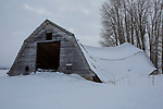 Montana, western, Flathead Valley, Kalispell. An old swaybacked barn in a snowy landscape.