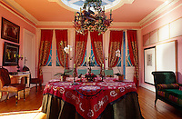 In this dining room stuffed parrots are incorporated into the 19th century chandelier that hangs above the dining table covered in a susani fabric