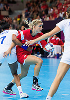 28 JUL 2012 - LONDON, GBR - Gøril Snorroeggen (NOR) of Norway (centre, in red) looks for a way through the French defence during their women's London 2012 Olympic Games Preliminary round handball match at The Copper Box in the Olympic Park, in Stratford, London, Great Britain (PHOTO (C) 2012 NIGEL FARROW)