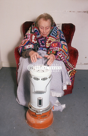 Elderly woman wrapped in blanket sitting in armchair in front of portable gas heater,