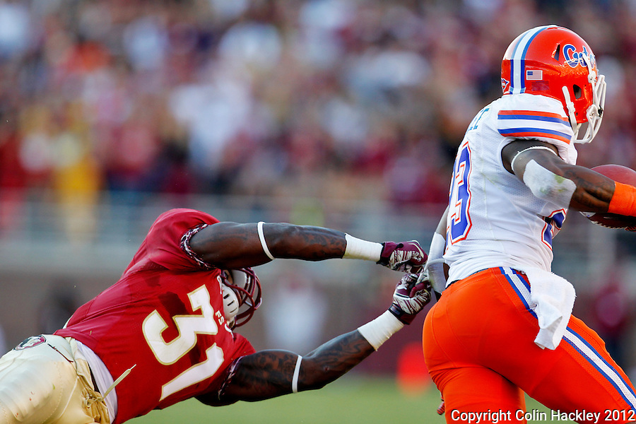 TALLAHASSEE, FL 11/24/12-FSU-UF112412 CH-Florida State's Terrence Brooks can't hang on to Florida's Mike Gillislee during first half action Saturday at Doak Campbell Stadium in Tallahassee. .COLIN HACKLEY PHOTO