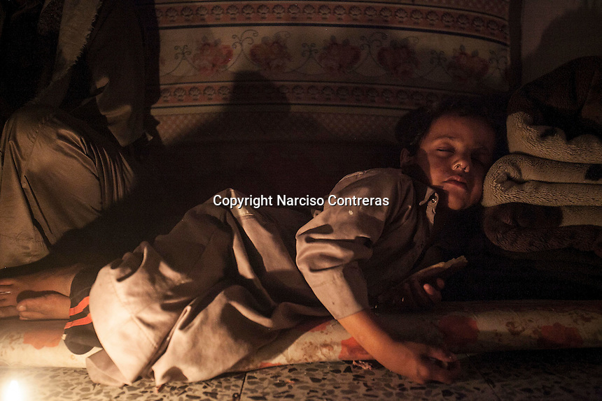 July 03, 2015 - Sana'a, Yemen: A son of Faud Hassan (not pictured) a 38 years-old bus driver from Sa'dah, sleeps after Iftar in a classroom used as temporary shelter for IDP's in Al Quds school in Sana'a. (Photo/Narciso Contreras)