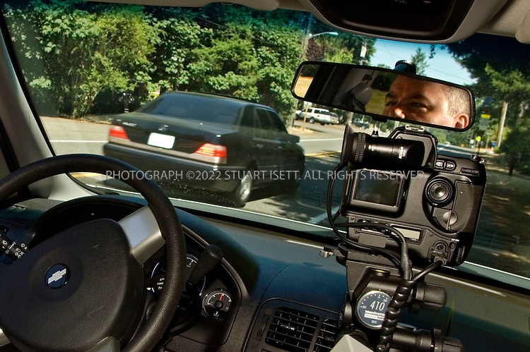 07/21/2006--Lakewood, WA, USA..Lt  Dave Guttu (seen in rear view mirror) of the Lakewood police department monitors traffic with the department's new camera-enforced radar trap that is installed in a mini-van parked along the sides of roads. As cars pass from behind they speeds are measured b y radar and a front facing camera then photographs the speeding car's license plate. The department purchased the system from Redflex in Arizona in May, 2006...Assignment ID: 30027119A..Photograph By Stuart Isett.All photographs ©2006 Stuart Isett.All rights reserved.