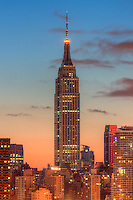 The Empire State Building during morning twilight as viewed over the Hudson River looking east from New Jersey.  The eastern sky and clouds were accented with tinges of orange that began to show in the hour before sunrise.