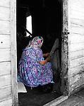 Dene elder scraping moosehide in shack