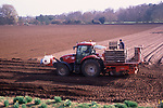 A913NF Tractor and trailer planting potato crop in field Suffolk sandlings England