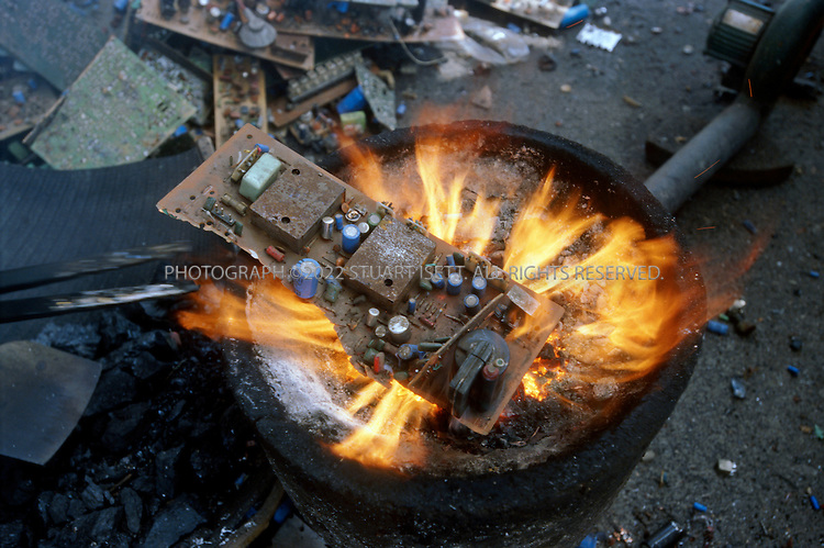 7/2/2005--Taizhou, Zheijiang Province, China..In the village of Mukeng, computer circuit  boards are 'cooked' down over charcoal burners to release chips and precious metals but also toxic fumes...The eastern Chinese port city of Taizhou has now become the center for much of the illegal trade in e-waste (computer waste). 24 hours a day ships arrive in the city?s harbor carrying cargo of waste, including millions of computer parts. These parts flow out of the port in trucks into the city and hinterland where hundreds of tiny work shops break down the parts, melting off the precious metals and using acids to separate gold from circuits boards, mobile phones, monitors and other computer parts. Neighborhoods are filled with the noxious and toxic fumes of this unregulated industry and thousands of men, women and children are exposed to a toxic cocktail of fumes and dust released. .Photograph By Stuart Isett.All photographs ©2005 Stuart Isett.All rights reserved.