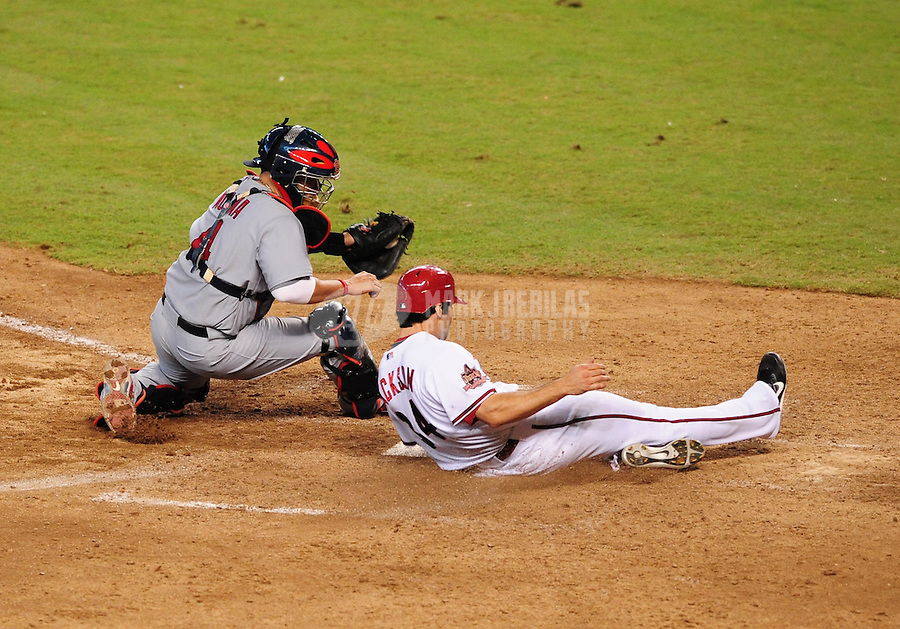 Sept 3, 2008; Phoenix, AZ, USA; Arizona Diamondbacks base runner (34) Conor Jackson slides safely into home ahead of the tag from St. Louis Cardinals catcher Yadier Molina to score the winning run in the ninth inning at Chase Field. Mandatory Credit: Mark J. Rebilas-
