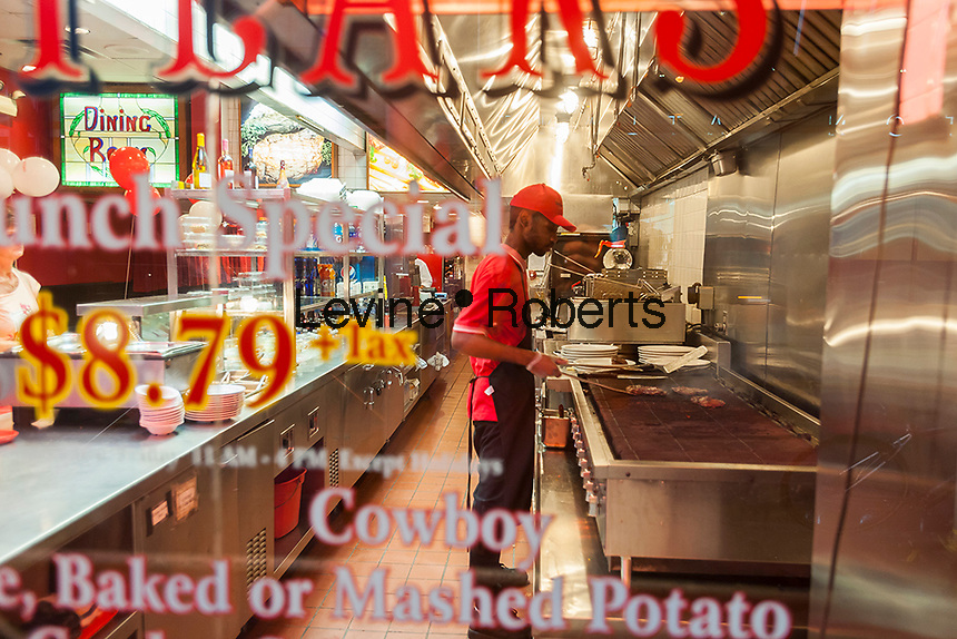 A cook prepares steaks on a grill in the window of Tad's Broiled Steaks in Midtown Manhattan in New York on Tuesday, September 6, 2016. Founded in 1957, the iconic chain is part of Riese Restaurants and this location is the only one left in New York. (© Richard B. Levine)