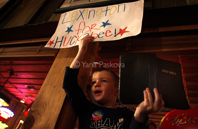 A boy holding a Bible and a poster supporting U.S. Presidential hopeful Gov. Mike Huckabee (R-AR) waits for him to sign the book at an event after the Michigan Republican Presidential Primary, (where his opponent U.S. Presidential hopeful Mitt Romney (R-MA) triumphed,) at Hudson's Smokehouse in Lexington, South Carolina, on January 15, 2008. (Photo by: Yana Paskova for The New York Times)..Assignment ID: 30055282E.....
