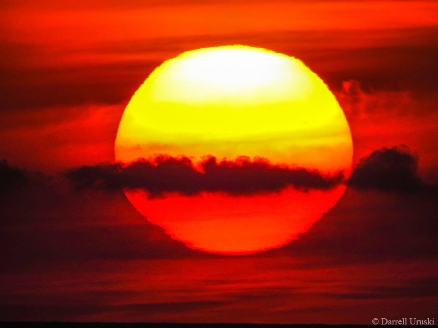 Sun in the Firmament of Heaven. <br /> A large scale photograph of a fiery red sun moving between the clouds right above the ocean just prior to it setting on the Pacific ocean.
