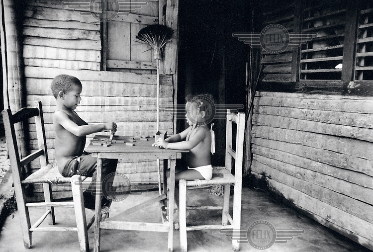 Lester Sosa (6) and Lucy (4) playing dominoes.?We like to play dominoes, just like our father.  He spends hours with his friends playing this game.  We think it?s really exciting.?