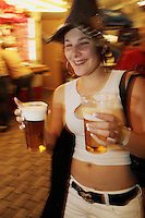 Switzerland. Canton Zürich. Winterthur. Oktoberfest. Bier fair. Cheers, Your health. A young woman carries plastic glasses full of bier in both her hands. She wears a hat on the head. Night life. © 2006 Didier Ruef
