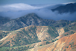 Coastal fog clouds rolling over rugged hikks on Santa Cruz Island, Channel Islands, California