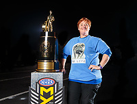 Nov 11, 2018; Pomona, CA, USA; NHRA photographer Rhonda McCole poses for a portrait with the championship trophy during the Auto Club Finals at Auto Club Raceway. Mandatory Credit: Mark J. Rebilas-USA TODAY Sports
