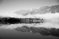 Black and White Photo of Misty Dawn Reflections on a Calm Lake Moke, Queenstown, South Island, New Zealand. Lake Moke, 10km from Queenstown is both a stunning lake and a department of conservation campsite (DOC campsite) with access for both caravans and campervans. In the early mornings Lake Moke is often perfectly still providing picture perfect reflections of the surrounding hills and mountains in the water. The combination of a fabulous golden hour as the sun rose over the hills, the morning mist lifting from the lake, and the rich, orange, autumn trees made this nights camping at the Lake Moke department of conservation campsite (DOC campsite) particularly special.