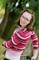 Young woman with glasses holding a bicycle..MR