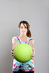 A young woman holding a green exercise ball