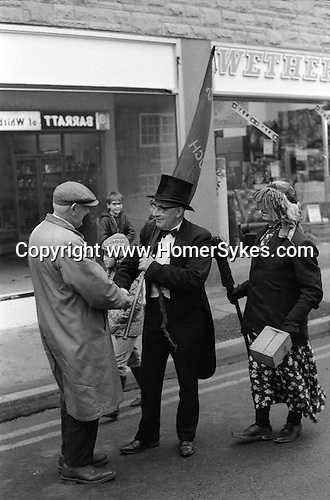Goathland Plough Stots.  Whitby north Yorkshire. England. 1972. Top hat leader and Betty or Betzy a man in disguise carry and broom and collecting alms.<br /> Mollie or Molly,woman played by a man past her prime.