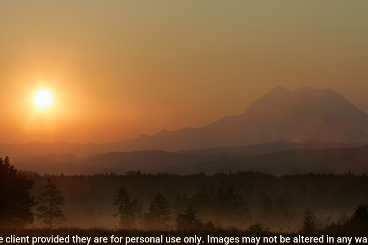 Mt. Rainier is a heavily glaciated, dormant volcano surrounded by alpine parks. The 14,411 foot volcano which covers 228,480 acres was designated a National Park in 1899. Misty sunrise seen through smoke from wildfires.  Jim Bryant Photo. ©2011. All Rights Reserved.