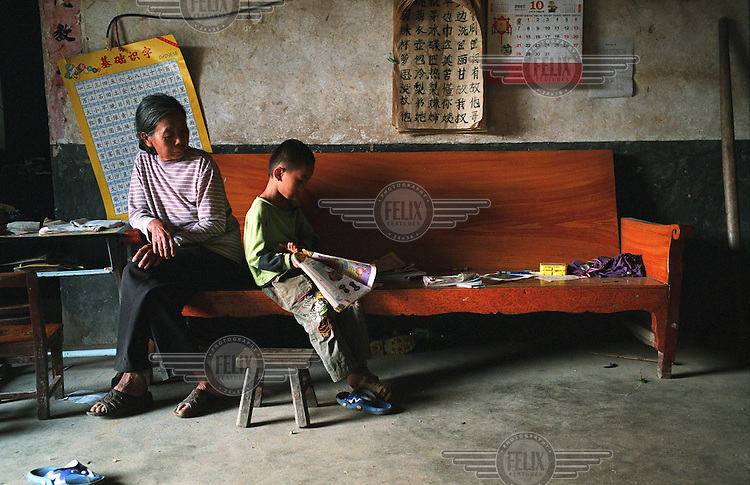 An elderly lady watches her grandson doing his homework at their village home near Yongle.
