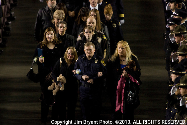 Family members carry stuffed animals as they leave a memorial service for slain Lakewood Police Department officers at the Tacoma Dome,  Dec. 8, 2009 in Tacoma, WA. Four Lakewood police officers were remembered at a memorial service that drew thousands of mourners. Tina Griswold along with sergeant Mark Renninger, officer Ronald Owens and officer Greg Richards were shot and killed at a coffee shop in the Tacoma suburb of Parkland, November 29 by Maurice Clemmons, who was later shot and killed by police.  Jim Bryant Photo. ©2010. ALL RIGHTS RESERVED.