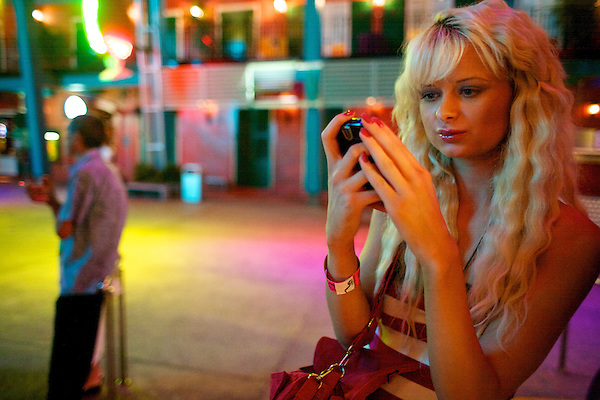 Paris Hilton impersonator texts on her Blackberry while waiting for friends