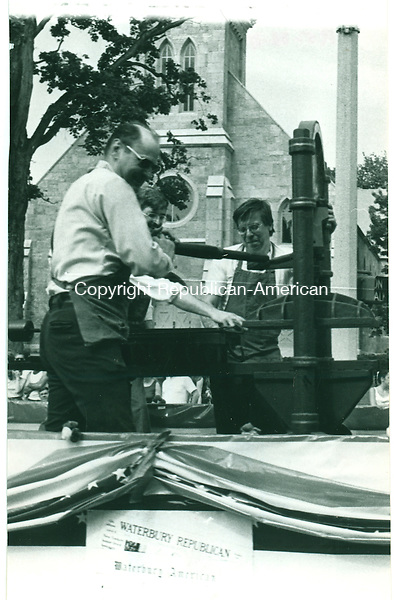 Printers Fred Daley, Jack Hoawrd and Don Creighton operate an antique printing press on a float sponsored by the Waterbury Republican-American in the Torrington Memorial Day Parade. 26 May 1981.