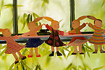 Paper dolls hanging in a window