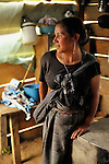 A woman and baby in the Guatemalan highlands near the family's newly constructed wood burning stove.  The concrete stoves,   are designed to be fuel efficient, requiring less firewood than open pit fires in the home or older, mud stoves.   This helps reduce deforestation and the burden of wood collection for families.  This stove, built in a side hut adjacent to the home, with a exhaust pipe, reduces health from traditional fireplaces on the floor inside huts.