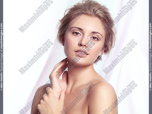 Beauty portrait of a young woman relaxed face with natural clean makeup and contemporary hairstyle over light pink flowy fabric background