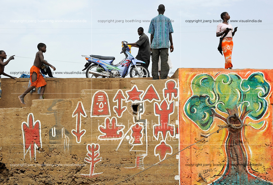 MALI Segou, quai with wall painting Dogon style and tree at river Niger