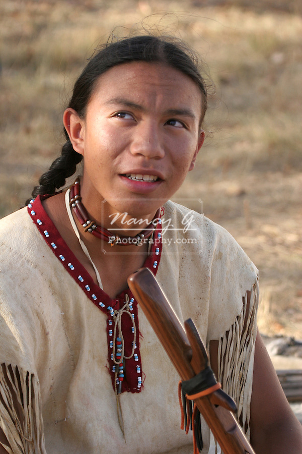 A Native American Indian boy holding a handcarved wooden flute