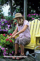 63821-14615 Woman sitting in yellow adirondack chair on deck trimming Geraniums  Marion Co.  IL
