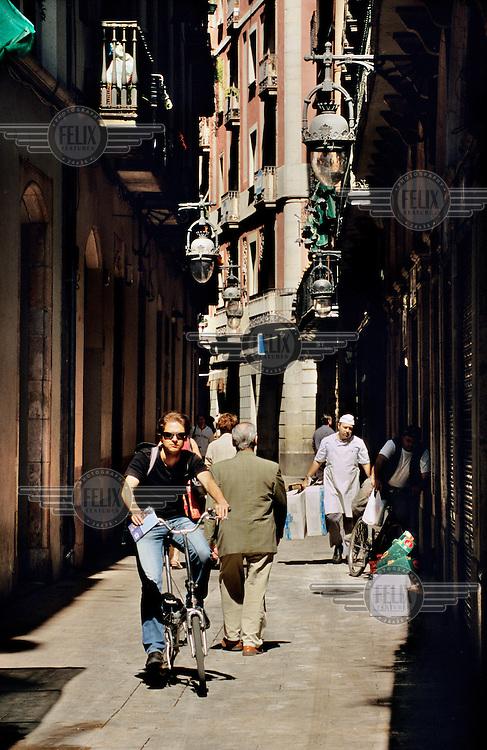 Man cycling through a narrow street in the historic Barri Gotic.