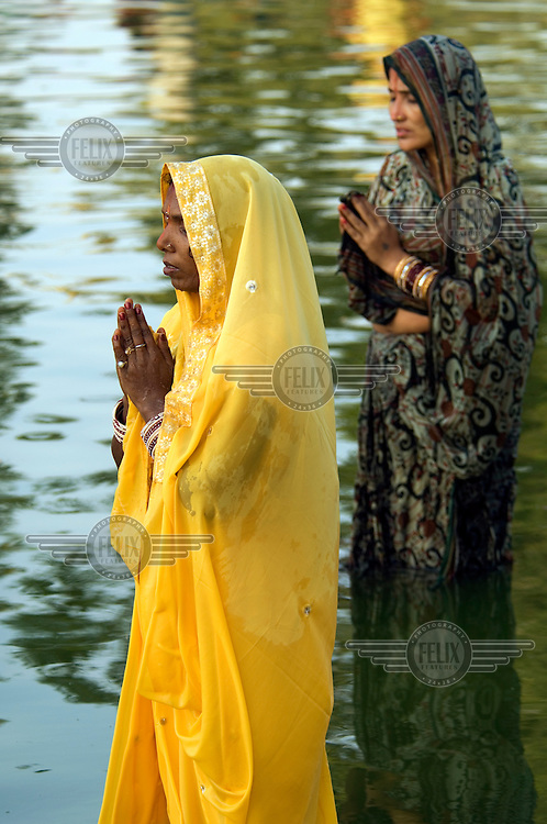 Women perform puja during a religious festival..
