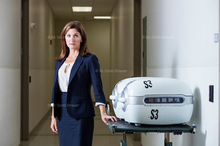 Alexandra K. Glazier is the President and CEO of New England Organ Bank, an organ procurement organization based in Waltham, Massachusetts, serving the greater New England area. She is seen here with two LifePort Kidney Transporters, also known as kidney pumps, that help keep donated kidneys viable during transportation.