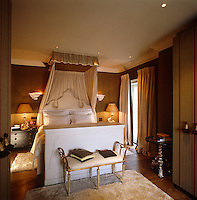 The bespoke bed in the master bedroom is decorated with a pleated half tester and a sculpted headboard