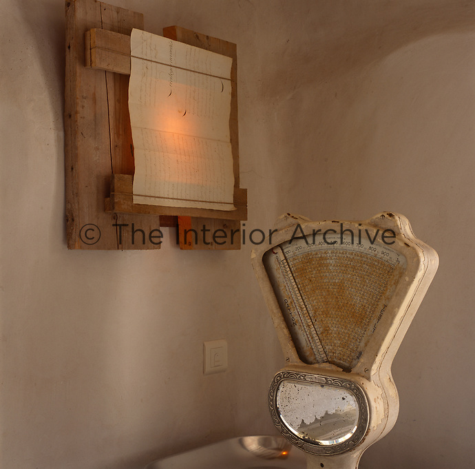 An old rusty weighing scale contrasts with a modern wall light made from a parchment mounted on rough wooden planks.