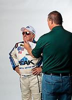 Feb 6, 2019; Pomona, CA, USA; Elon Werner (right( adjusts the face of NHRA funny car driver John Force as he poses for a portrait during NHRA Media Day at the NHRA Museum. Mandatory Credit: Mark J. Rebilas-USA TODAY Sports