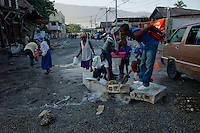 Port Au Prince, Haiti, Jan 25 2010.Water ressources are scarce in Port au Prince, people are collecting water from a bust underground pipe..